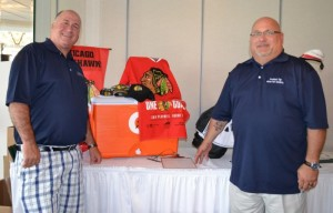 Jim Romanek (left) and Committee member Dennis Bagdon  take time out for a photo in front of an auction prize. Dennis sponsored a hole in memory of his daughter Megan who benefitted from the services provided by the Treasure Chest Foundation.